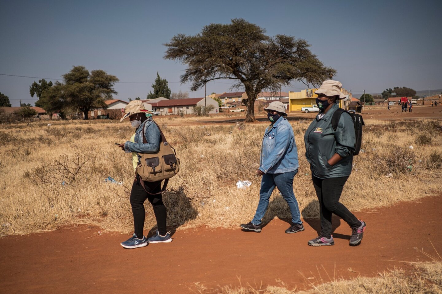 Community Healthcare Workers, Thatayaona Gaebetse (35), Emily Mkenku (55) and Kereng Motlhale (44) walk to homes to do tracing in the community close to the Pudumong Healthcare Centre in the North West Province, South Africa, on Sept. 4, 2020. | TRF