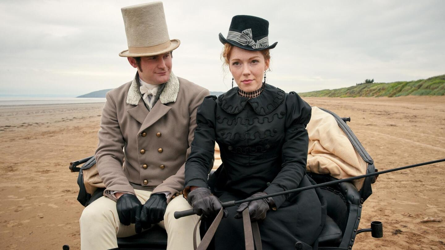 """A man and woman sit in a carriage in the middle of a sandy landscape. 