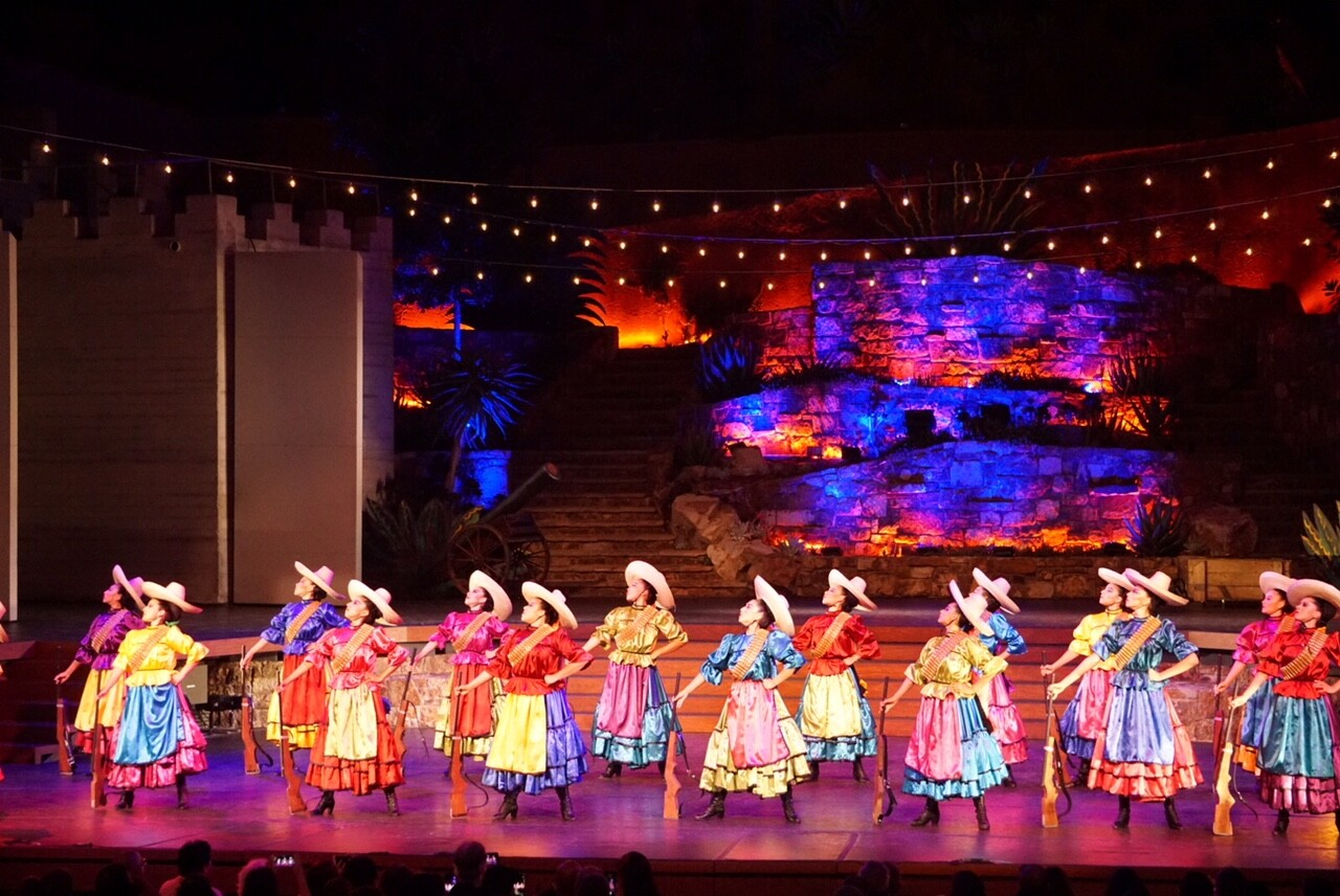 """La Adelita"" performed by Pacifico Dance Company showcases the role of women int he Mexican Revolution. Female dancers with sombreros and and guns stand proudly in formation. 