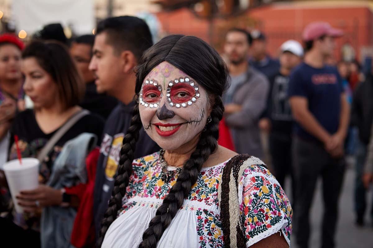 A young woman in calaveras paint smiles during the Día de los Muertos celebration in 2019  | Pablo Aguilar