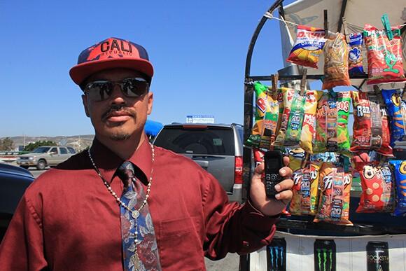 Mercado de Artesanias de La Linea vendor listens to the conversation on his cell phone radio. San Ysidro Port of Entry, Tijuana.