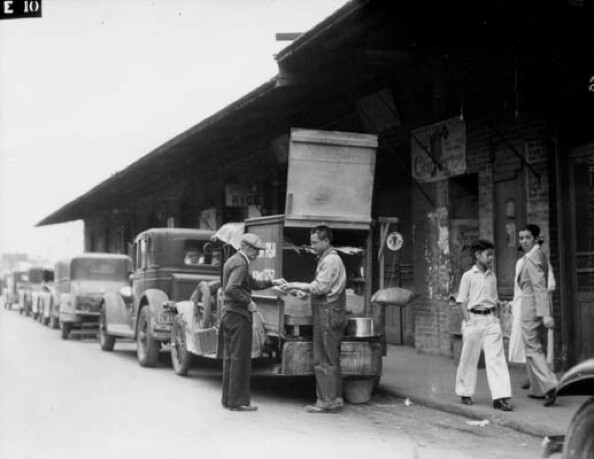 A fish vendor sells fresh fish to a Chinatown local from the back of his truck. | Courtesy of the Los Angeles Public Library