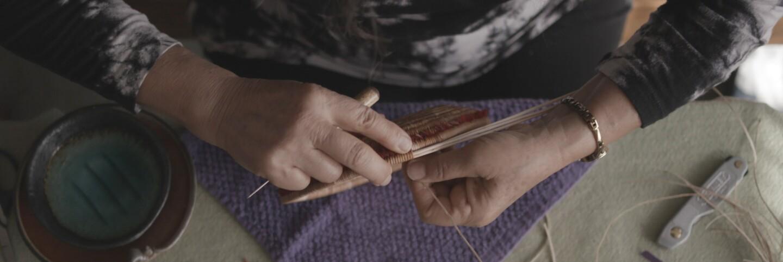 """Linda Yamane making a basket   Still from KCET Artbound's """"The Art of Basket Weaving"""""""