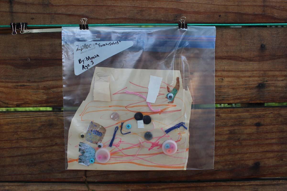"""""""Fauxlijolij"""" a piece made of found objects resembling fish by child artist Mona hangs on Dan Fields' Los Feliz fence gallery."""