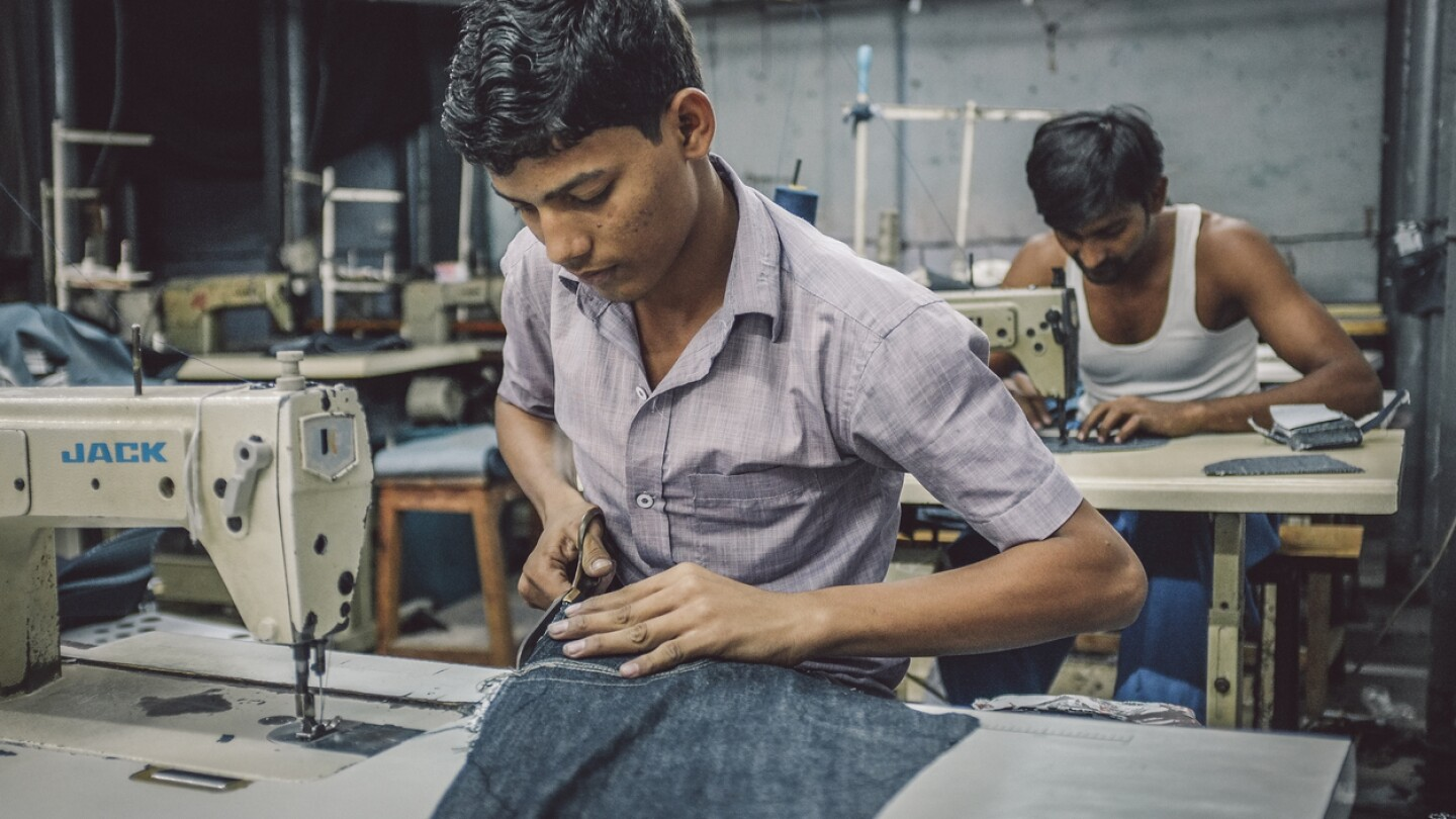 Indian workers sew in clothing factory in Dharavi slum
