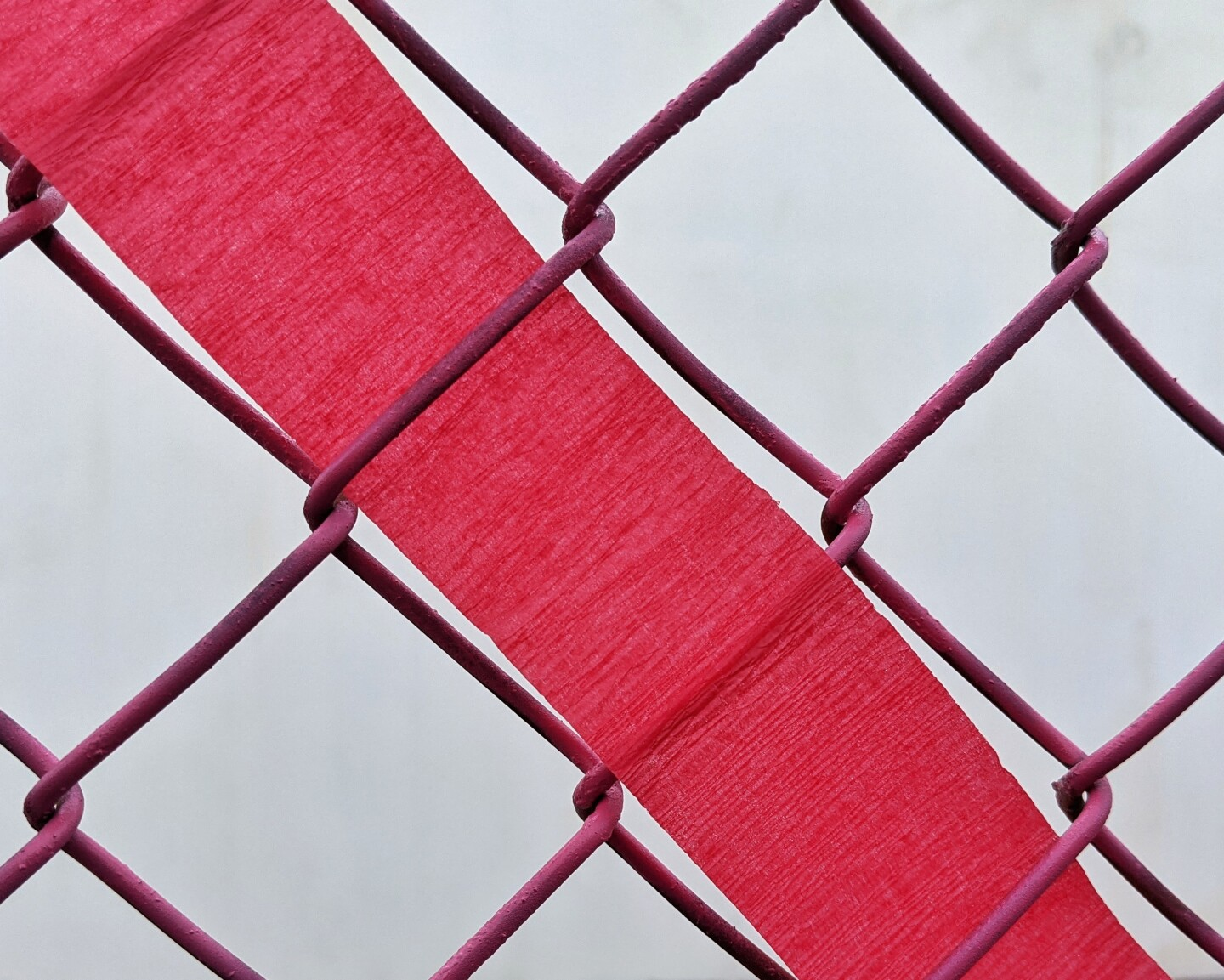 A piece of red streamer paper is woven through a fence.