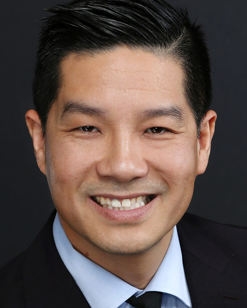 Tam Nguyen smiles in a suit and tie