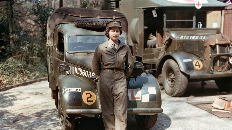Queen Elizabeth II in war uniform stands in front of a vehicle.