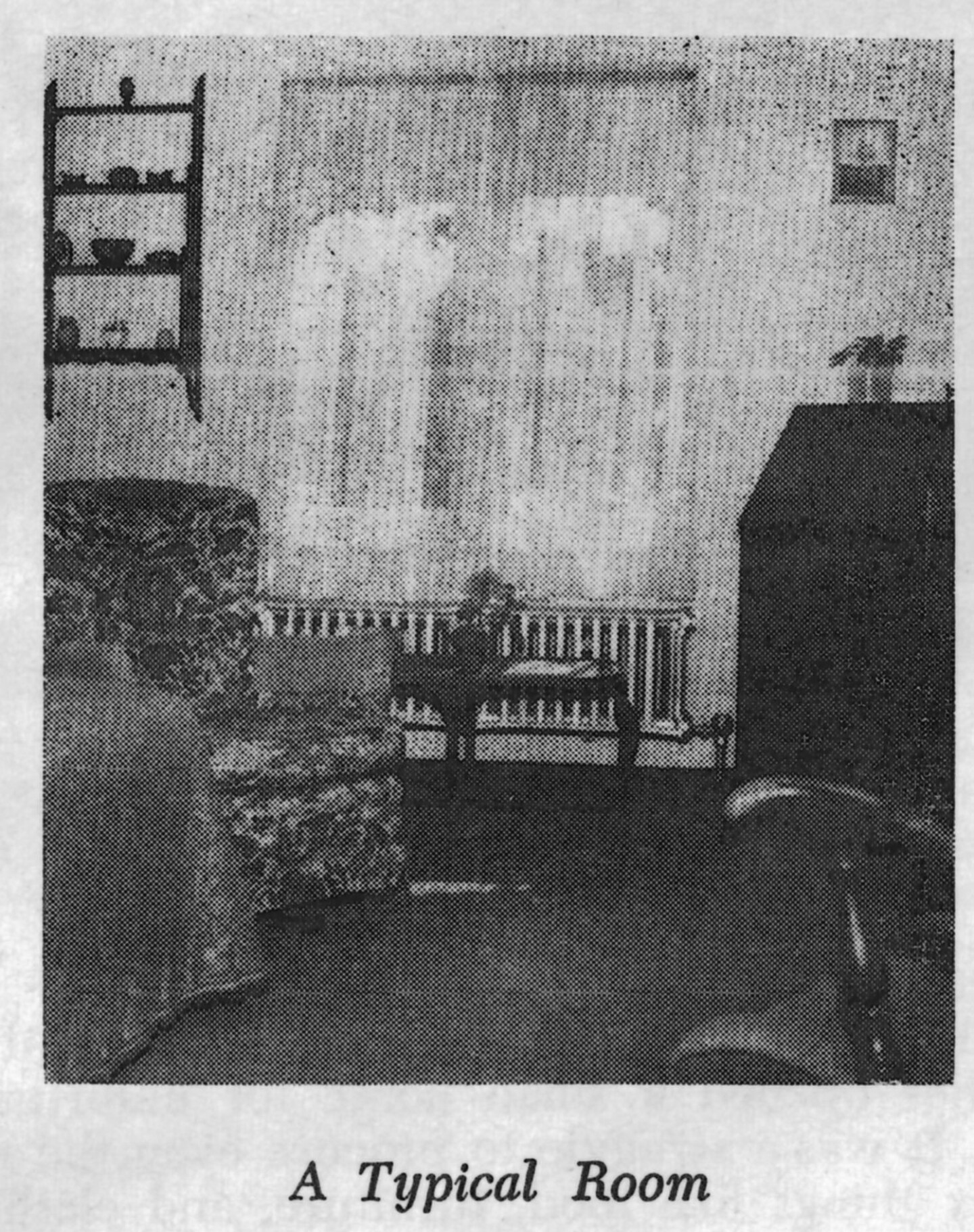 A black and white photo of a single room at the Woman's Christian Temperance Union Home. There is a floral arm chair, shelving with various items and a big window with sheer curtains.