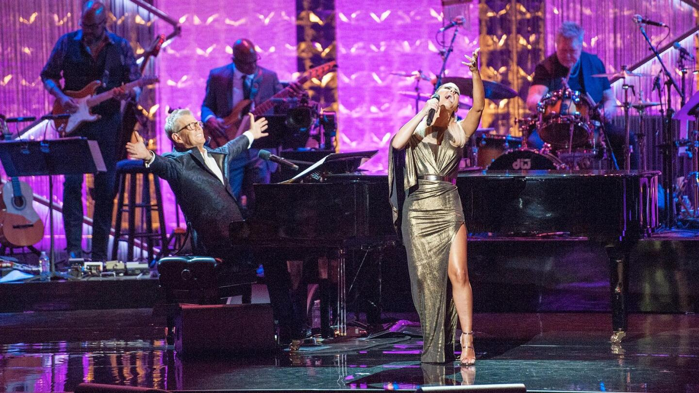 "David Foster reaches out his arms at his piano, while a performer belts out a high note. | ""Great Performances: An Intimate Evening with David Foster"""