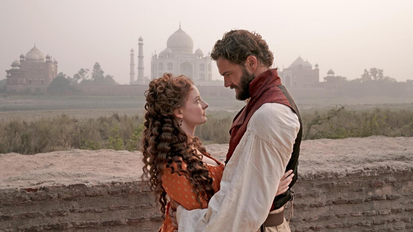"""A man and woman embrace each other, with the Taj Mahal in the distance. 