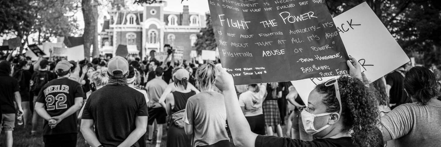 Woman holds a poster describing the need to fight the abuse of power in a demonstration to protest the killing of George Floyd in Des Moines, Iowa. | Phil Roeder/Flickr/Creative Commons License