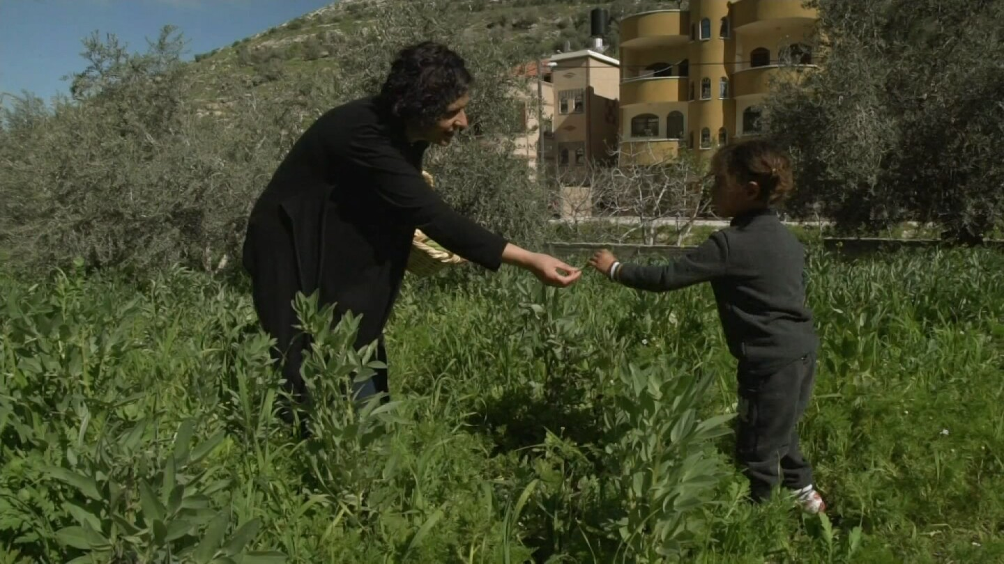 "Woman in a garden hands something to a young girl. | Still from ""Witness"" episode ""The Seed Queen"""