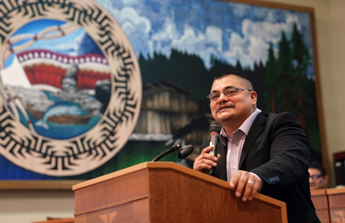A man in a black suit jacket and glasses speaks at a podium with a Yurok seal in the background.