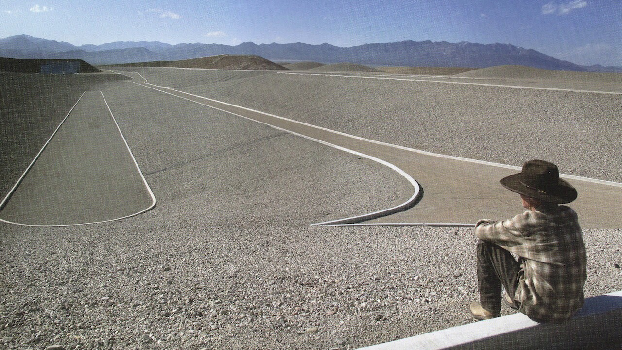 Michael Heizer sits on the ledge of one of his City installations.