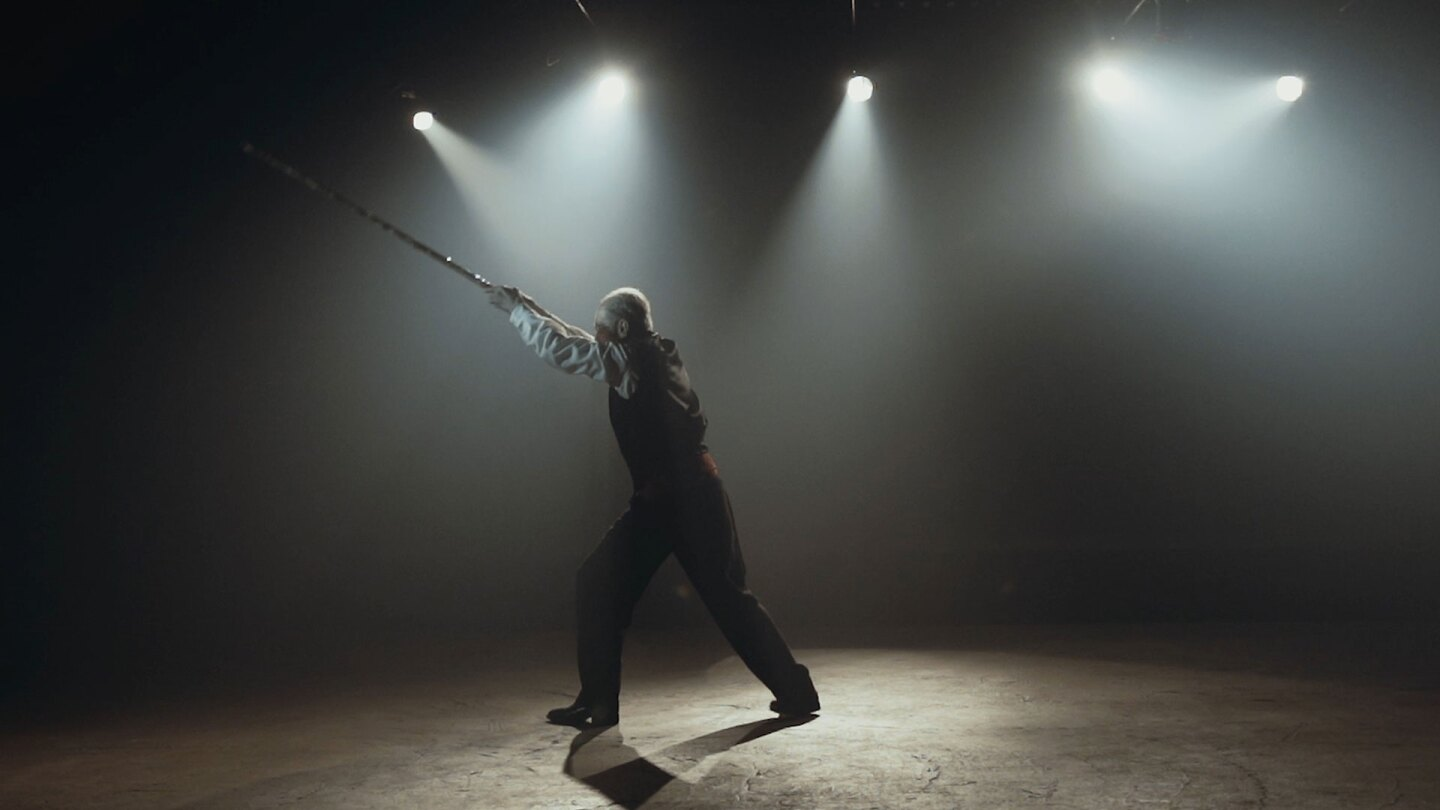 Still from Border Blaster Video: Person on a stage with spotlights thrusts a long object into the air