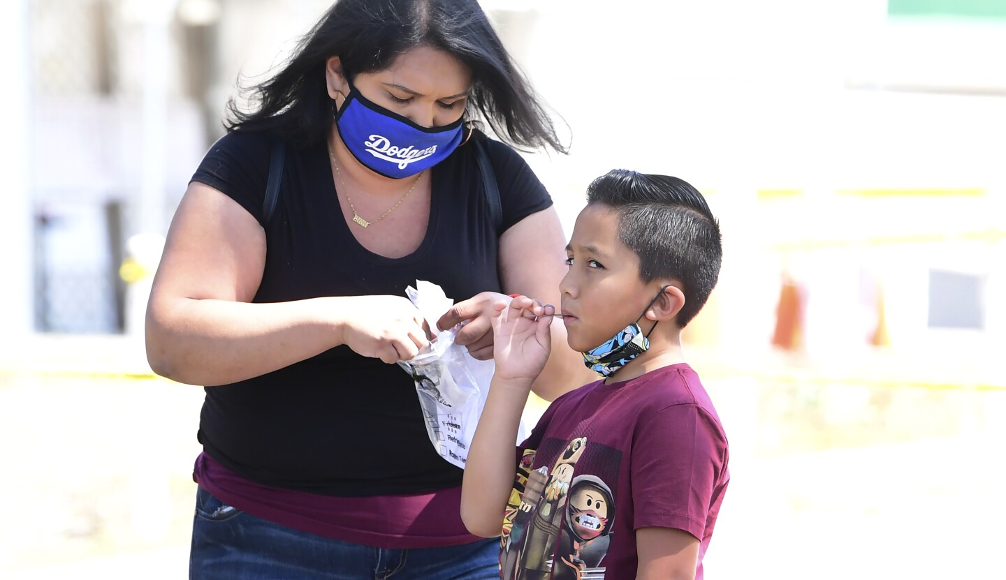 A child takes a COVID-19 test at a walk-in COVID-19 test site in Los Angeles, California on July 17, 2020.