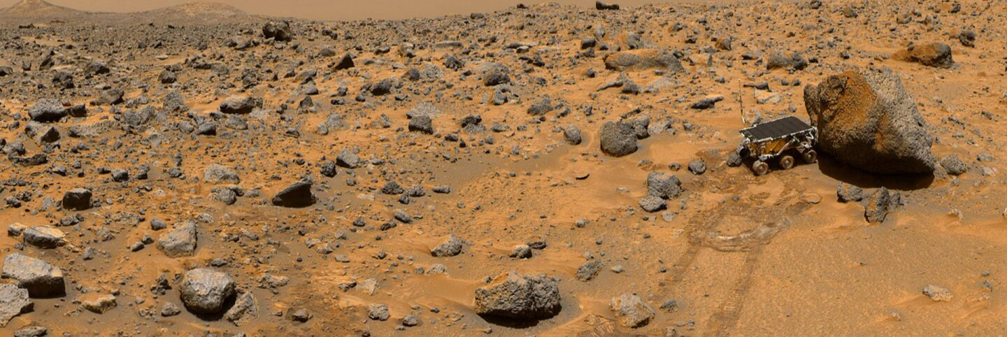 """This portion of a classic 1997 panorama from the IMP camera on the mast of NASA's Mars Pathfinder lander includes """"Twin Peaks"""" on the horizon, and the Sojourner rover next to a rock called """"Yogi."""" 
