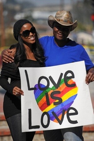 A lesbian couple hold a sign at a protest outside the County ClerkÂ's Office in Los Angeles on Valentine's Day | AFP/Getty Images
