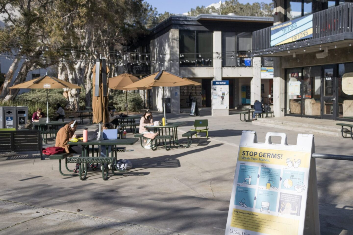 Students study outdoors in Muir Quad at UC San Diego on Feb. 17, 2021. A sign outlines the correct hand-washing procedures to fight COVID-19.