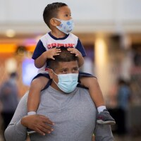During the global coronavirus Mario Tejada walks with his son Mario Tejada, Jr. age 3, on his shoulders both wearing masks in Tom Bradley international at LAX on Tuesday, Nov. 17, 2020 in Los Angeles. | Francine Orr / Los Angeles