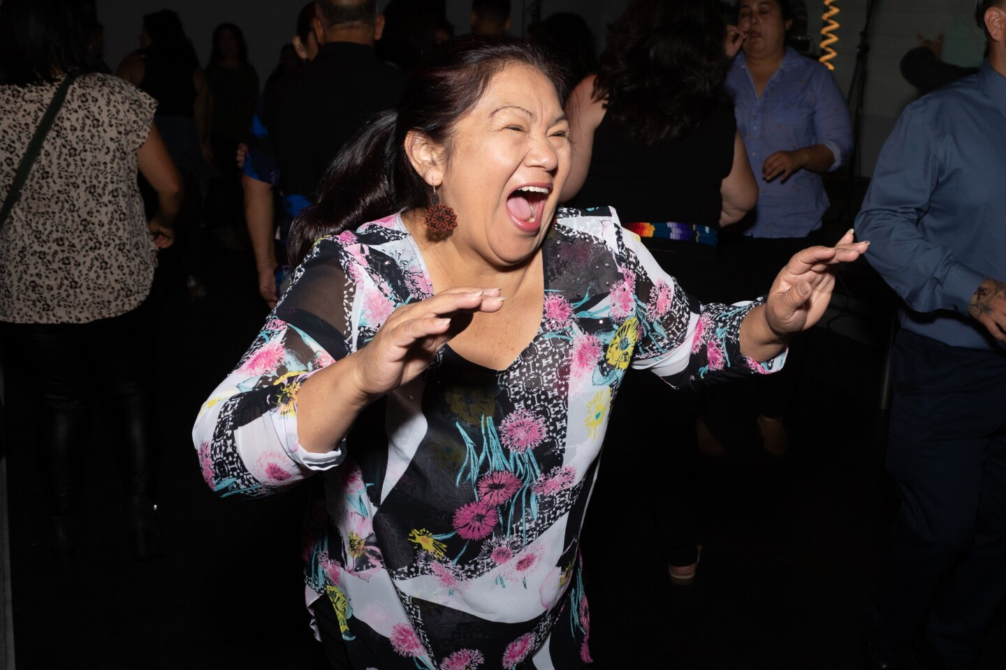 A lady in a flower shirt expresses joy at Cumbiatón.
