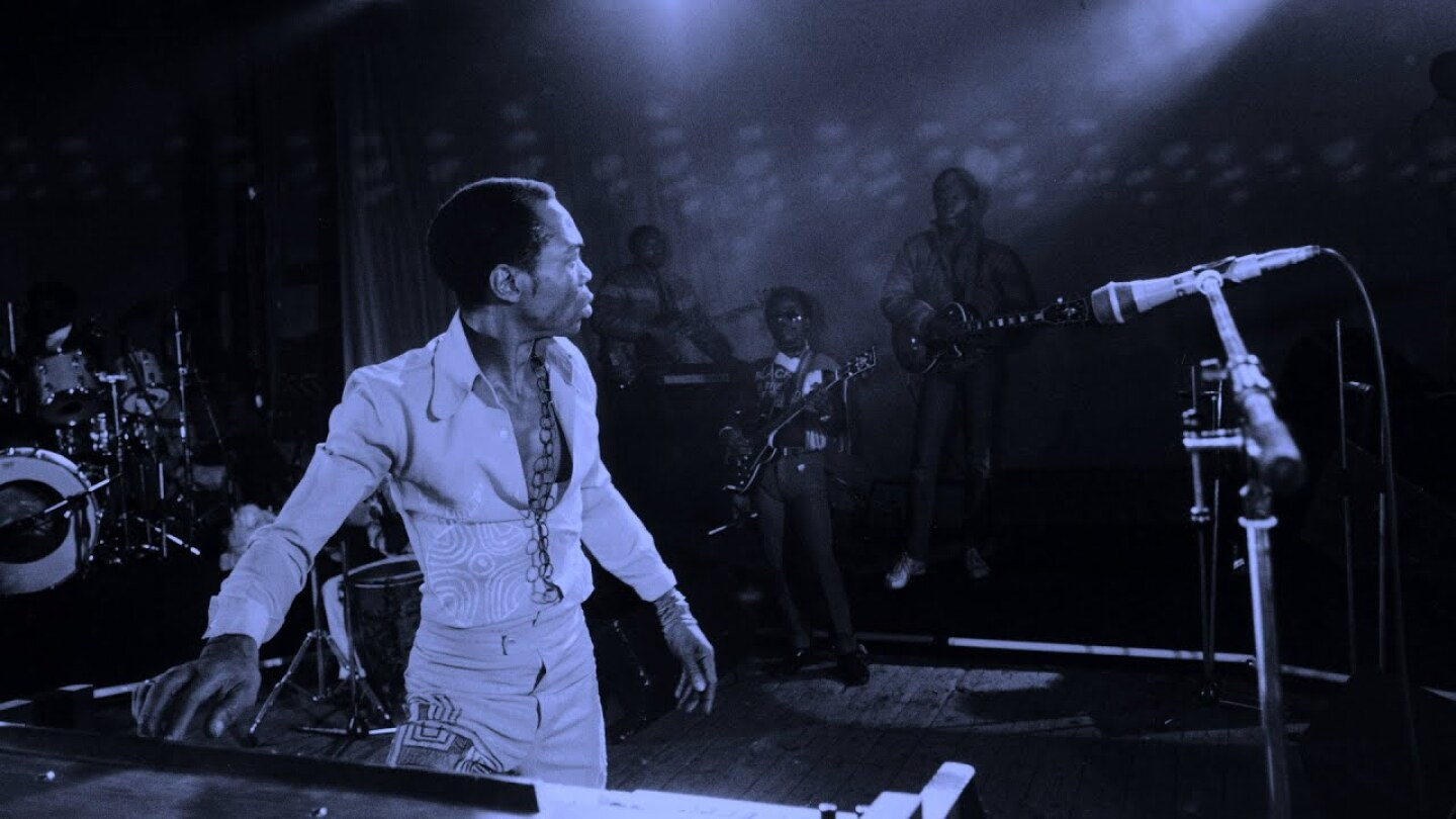 Fela Kuti performing on stage.