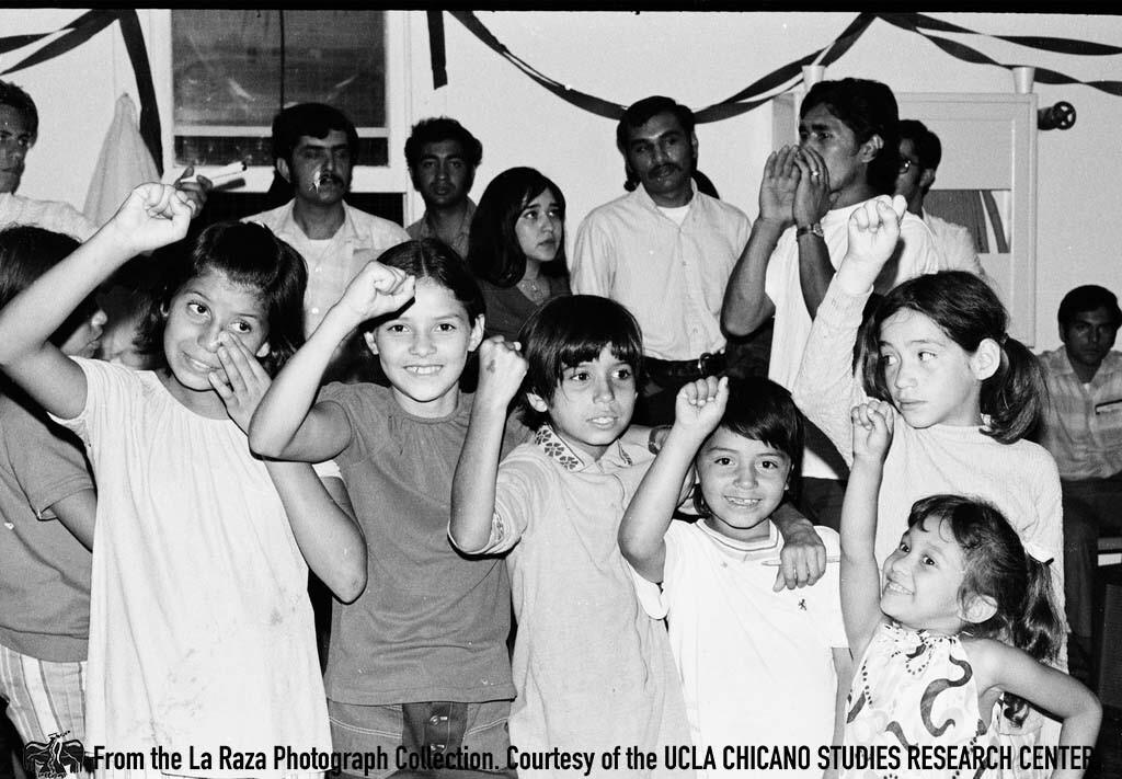 CSRC_LaRaza_B11F13C3_RR_023 Children at a musical performance by Estudiantina de la Facultad de Ingenieria from UNAM | Raul Ruiz, La Raza photograph collection. Courtesy of UCLA Chicano Studies Research Center