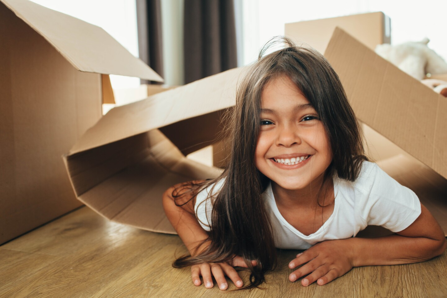 little girl playing with Cardboard Box, into her new house.