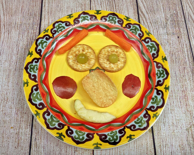 Una carita felíz hecha de comida sobre un plato amarillo.