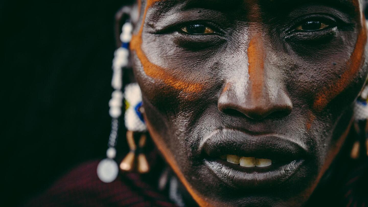 """A closeup portrait of a man wearing traditional face paint. 