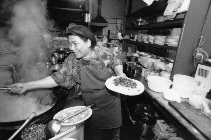 Black and white photo of a woman reaching over a pot in a steamy kitchen