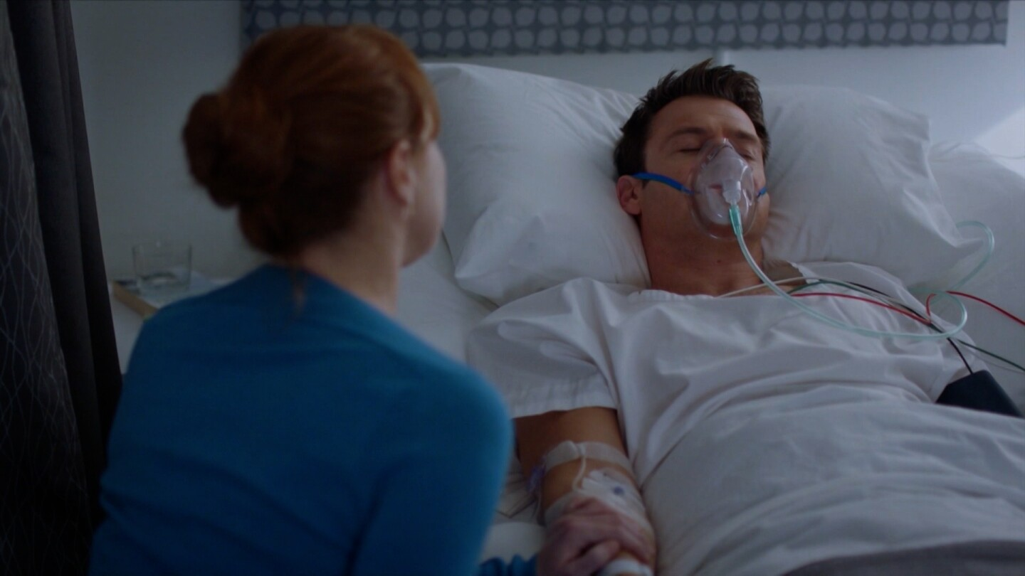 "A woman sits by a man lying in a hospital bed and wearing an oxygen mask. | From ""The Heart Guy: S2 E9"""