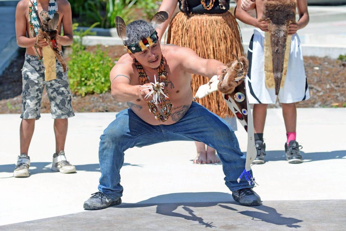 A shirtless man in jeans and sneakers wears Indigenous Yurok decorations like a necklace and headband as he performs a Brush Dance demonstration outdoors.