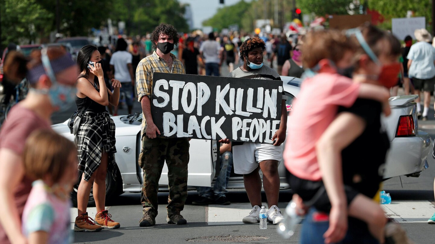 """Two protesters wearing face masks hold a sign that says """"Stop Killin' Black People"""" among a crowd of people. 