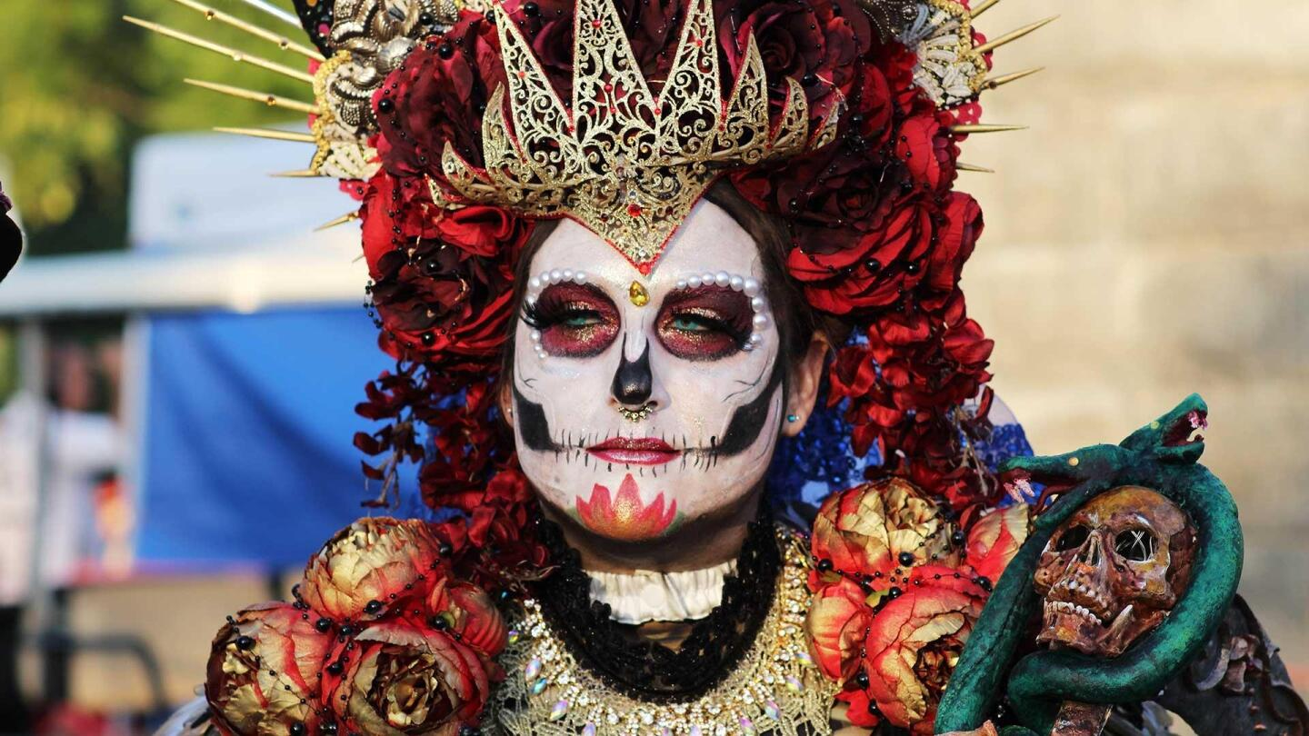 A photo of someone dressed vibrantly and wearing intricate face painting for Día de Los Muertos.
