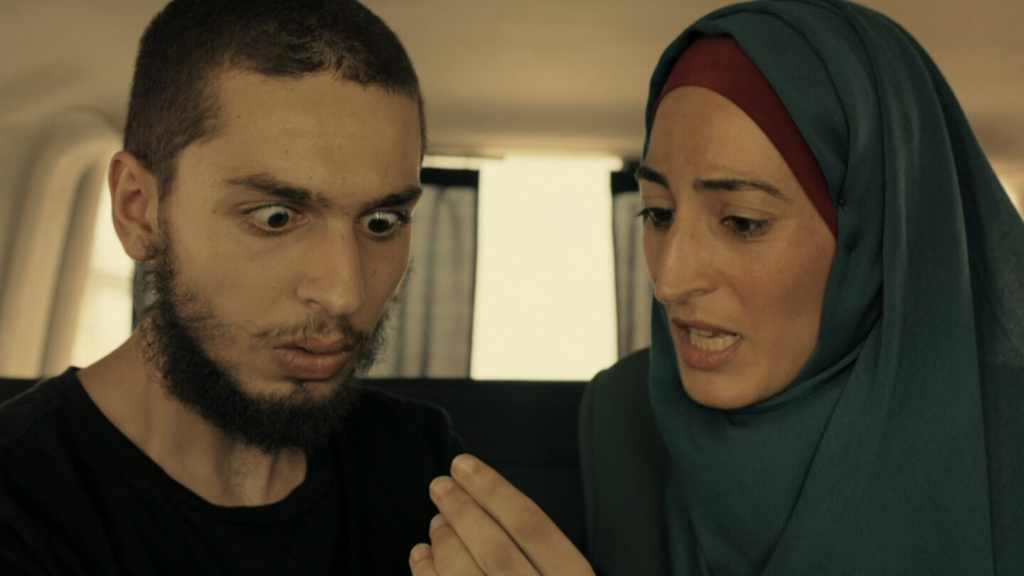 """Man with his eyes widened at something a woman wearing a hijab is holding. 