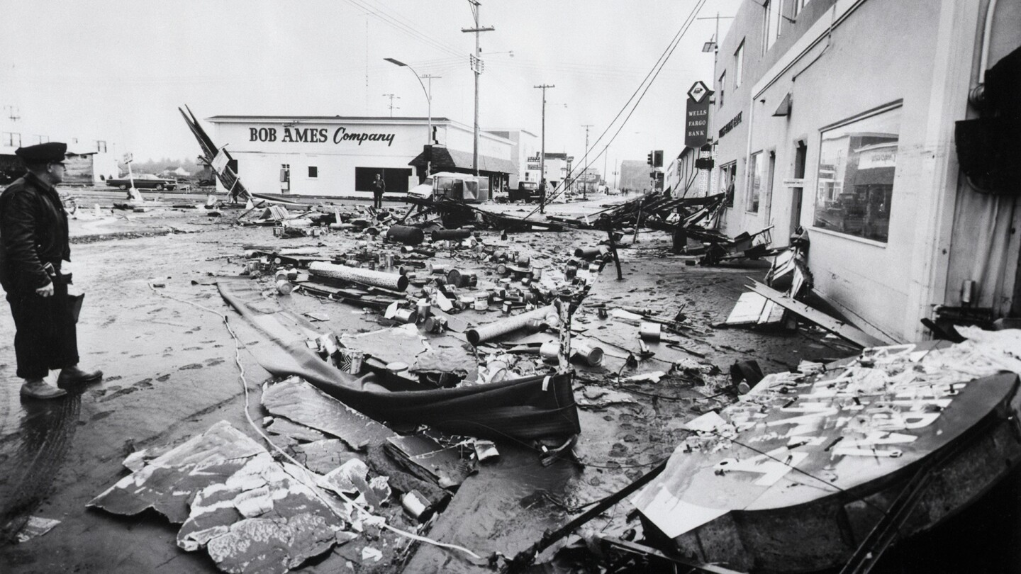 3/28/1964-Crescent City, CA- Unidentified man (l) stands amid debris-ridden city where martial law was declared after tremendous tidal waves from the Anchorage, Alaska earthquake destroyed 150 businesses and killed at least nine persons. Twelve-foot tidal