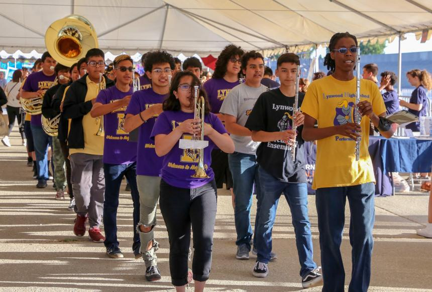 Young people with wind instruments march down in a parade.