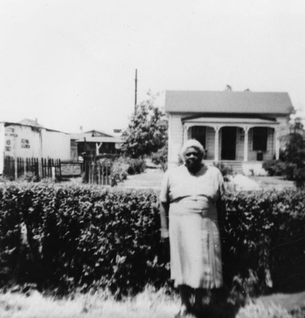 Woman stands in front of a home at 48th Place and Compton Avenue. Photo coutresy of the Los Angeles Public Library, Shades of LA collection.