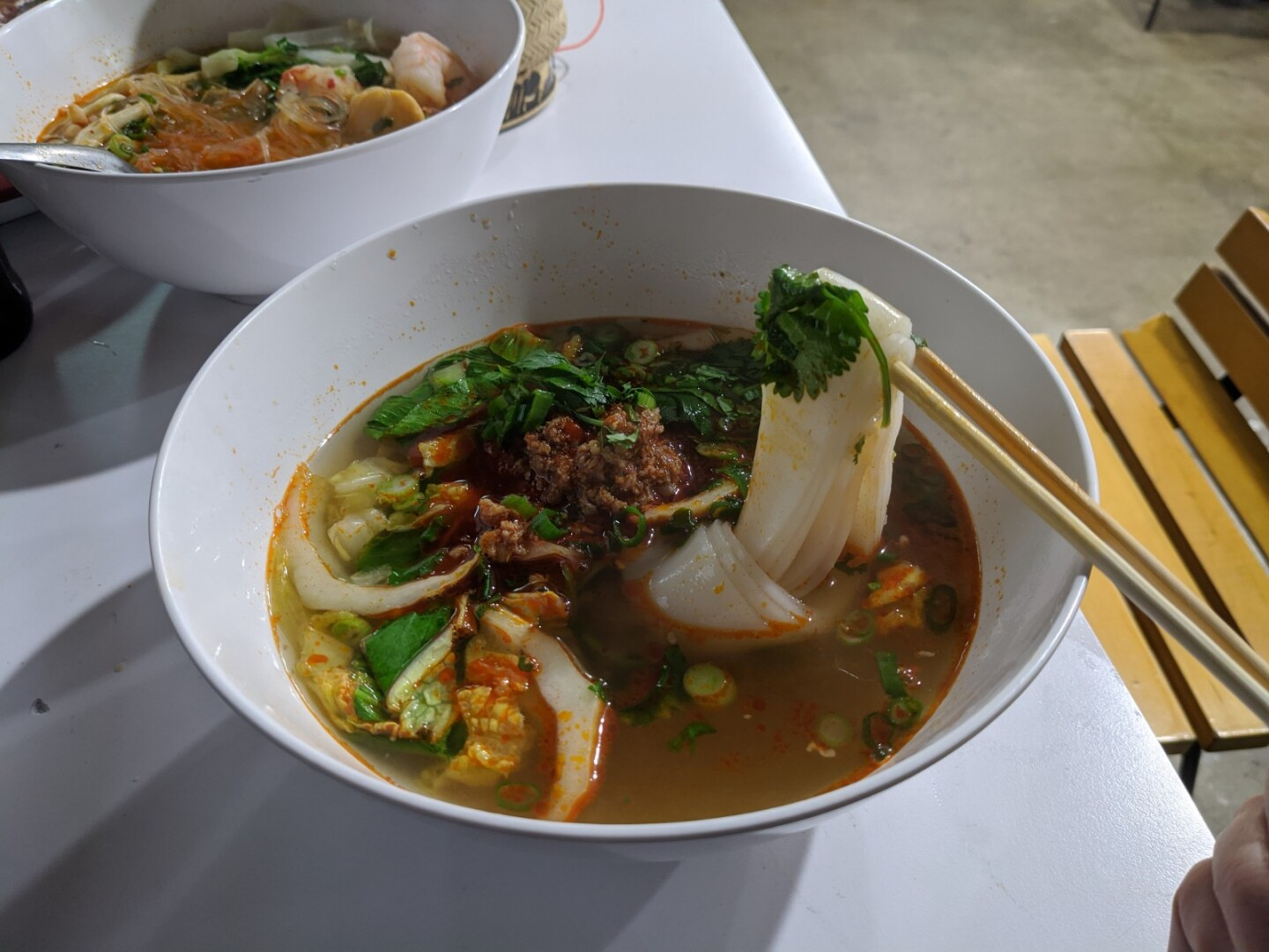 A bowl of khao soi, rice noodle in a clear pork broth underneath sautéed fermented soybeans, dried chilis and minced pork.