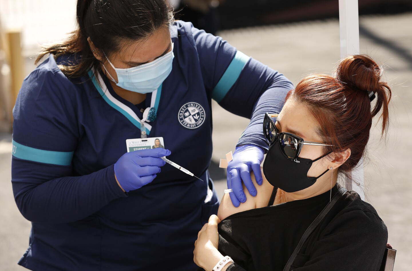 A woman in a black t-shirt gets a vaccine administered on her right arm by a woman in dark blue scrubs.