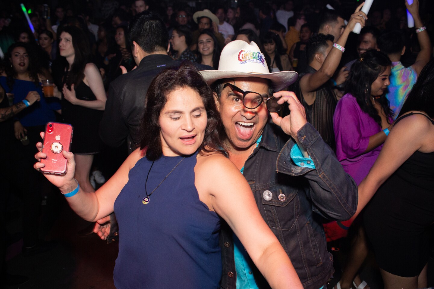 A woman in a purple top and a man in a cowboy hat dance at Cumbiatón