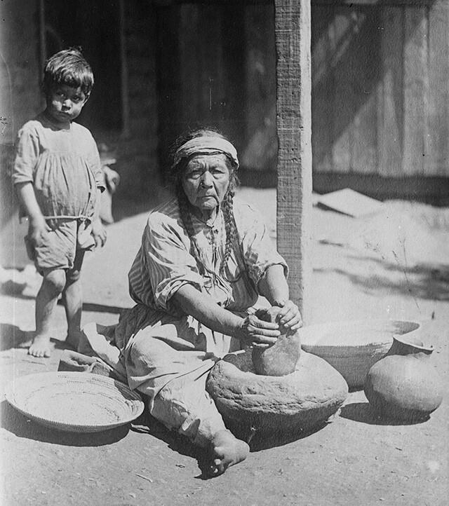 Paiute woman grinding meal on stone metate, Nevada (1900) | Huntington Library