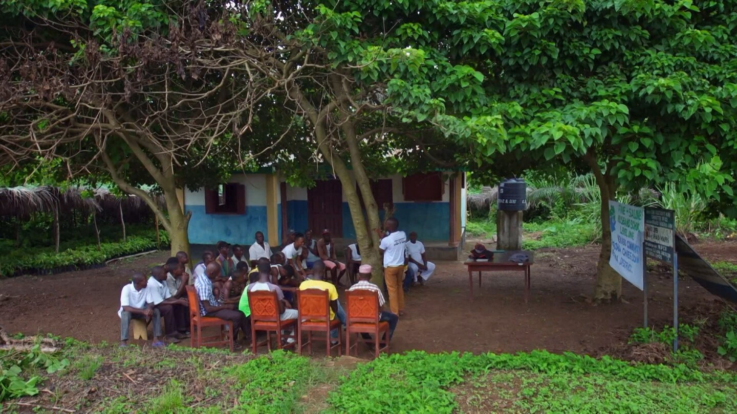"Group of men sit in outside classroom surrounded by trees. | Still from ""The Husband School"" episode of ""Witness"""