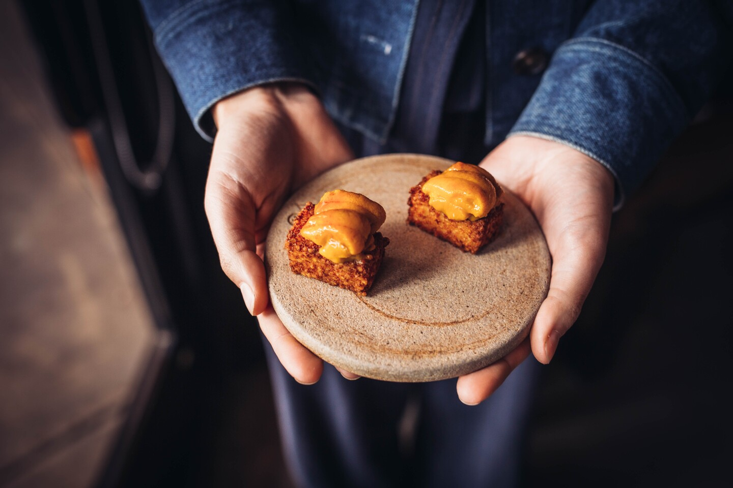 Two bite-sized food sit on a small, smooth ceramic plate. An orange, creamy slab of umi sits on top of a cube-shaped deep-fried tapioca.