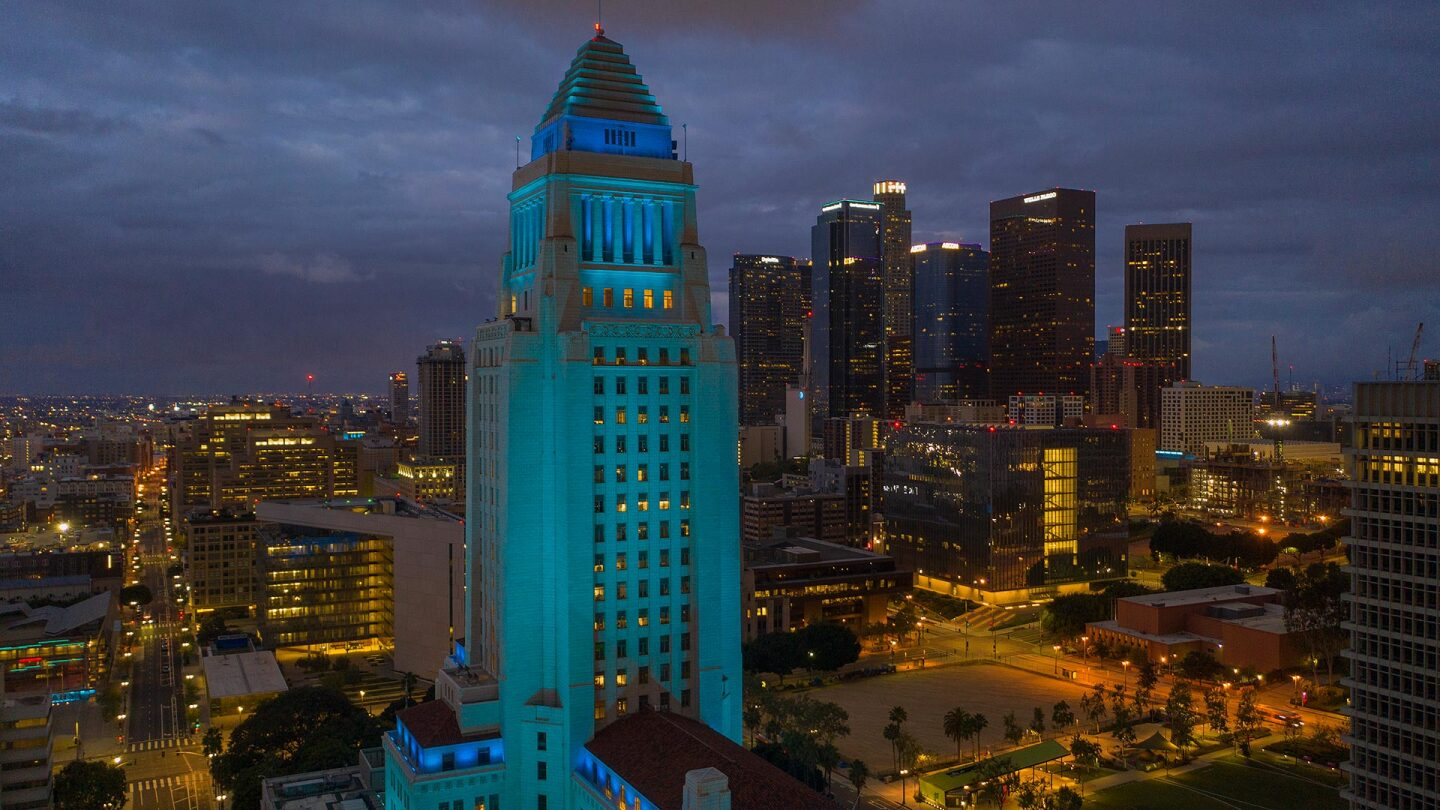 An aerial view shows Los Angeles City Hall illuminated in blue as a tribute to healthcare workers responding to the coronavirus pandemic on April 18, 2020 in Los Angeles, California.