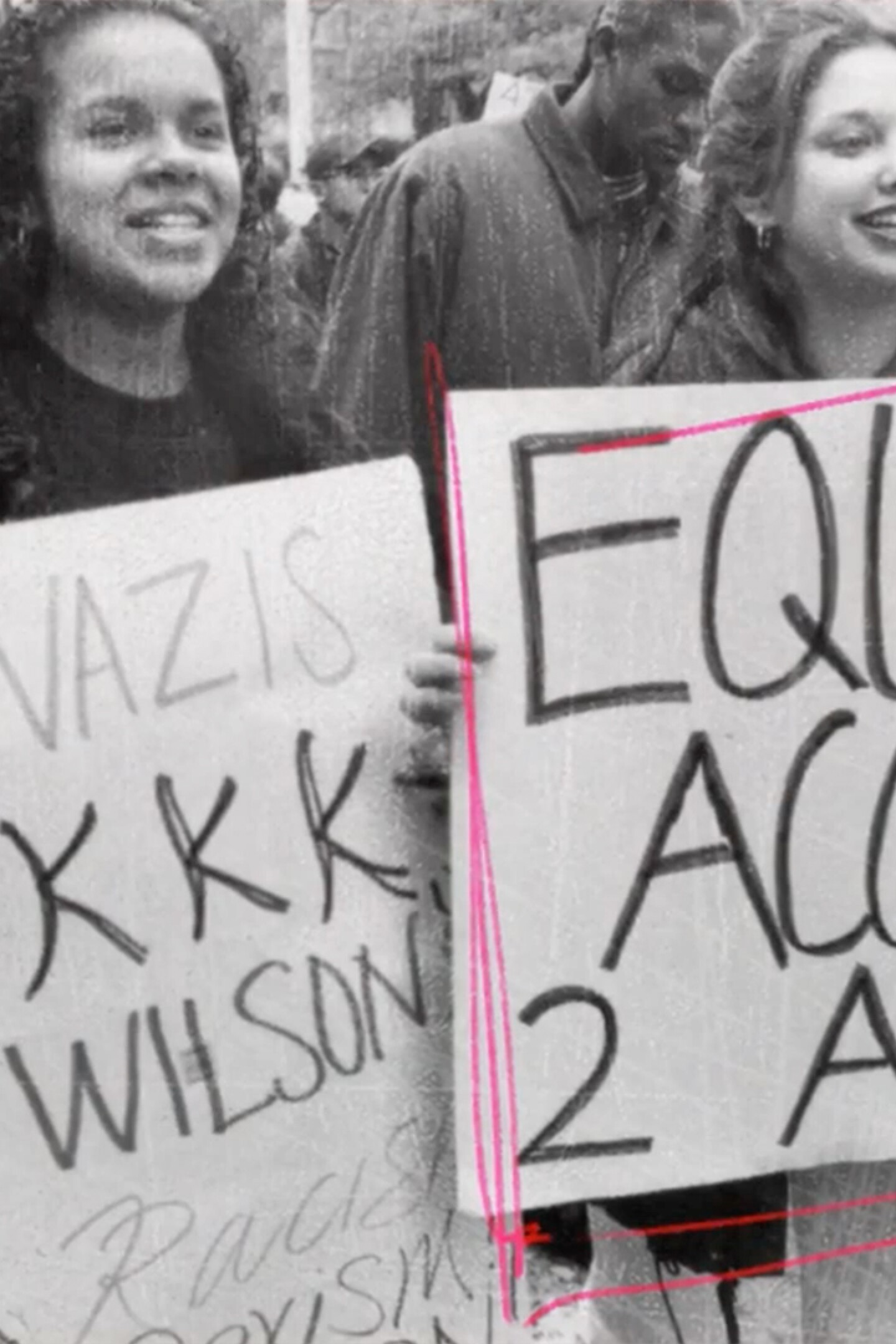"""Two women hold signs protesting Proposition 187    Still from """"187"""""""
