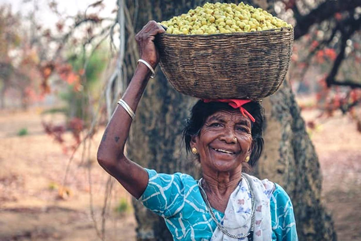 A basketful of mahua flowers brings a smile to a woman in Budhiarmari village in Chattisgarh state, India, India, Nov. 13, 2020. | Thomson Reuters Foundation/Purushottam Thakur