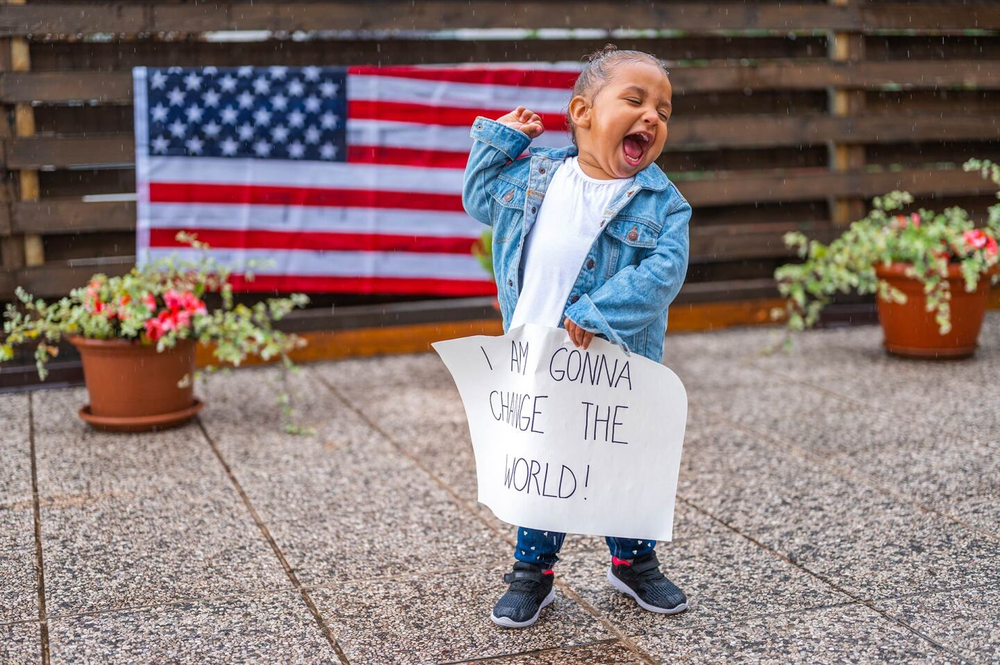 """A small child holds their fist in the air and holds a sign that reads """"I'm gonna change the world."""" 